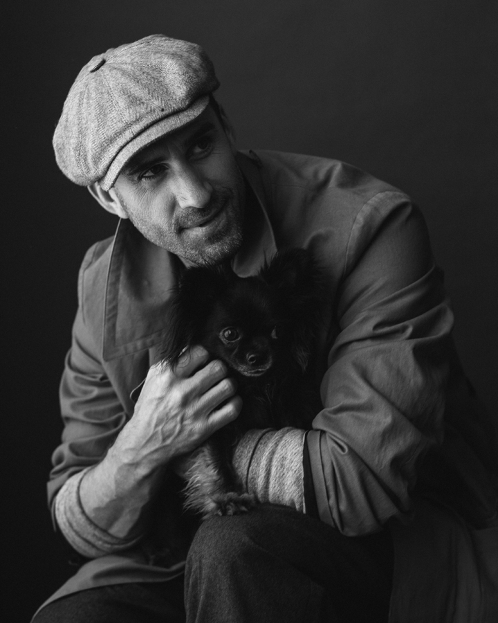 Photo of Actor Joseph Fiennes, from Handmaid's Tale photographed in studio in black and white. Wearing APC, Billy Reid. Actor hold black chihuahua named Vader.