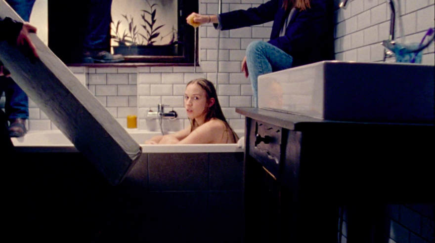 Image of model Sára Szőke in a bathtub with set design. Set designer dripping water on head.