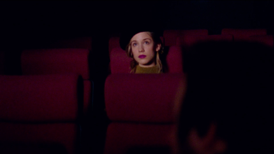 Image of Sára Szőke in a dark movie theater looking at the screen.