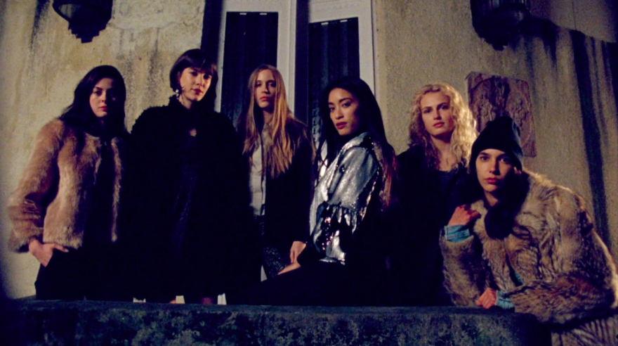 Image of 6 girls looking straight at camera. Standing and sitting outside in the dark.