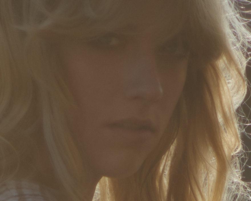 Close up of model Emma Surmon. GIrl in sunglight, fashion shoot