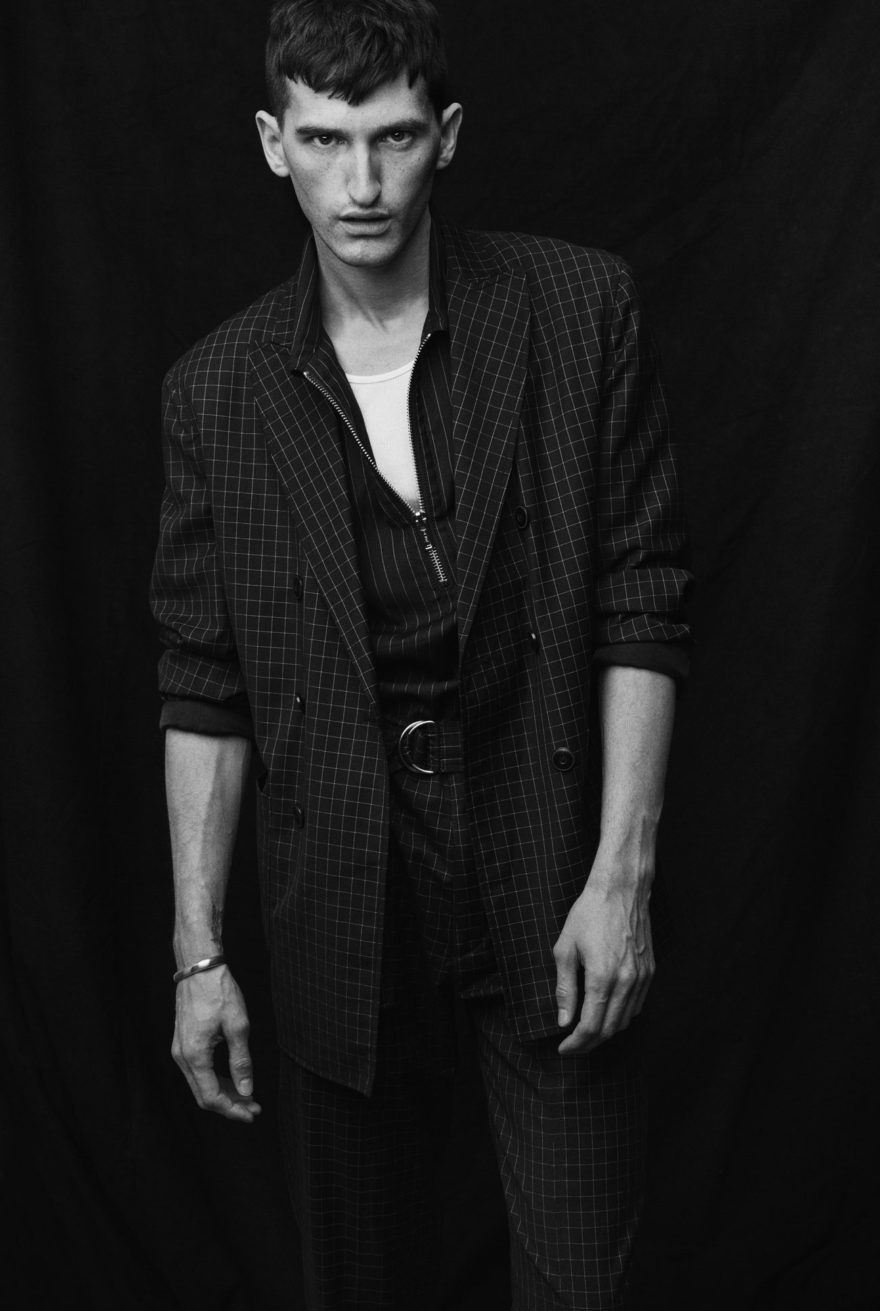 Male Model Andy Nordin stands in a photo studio in black and white photo.