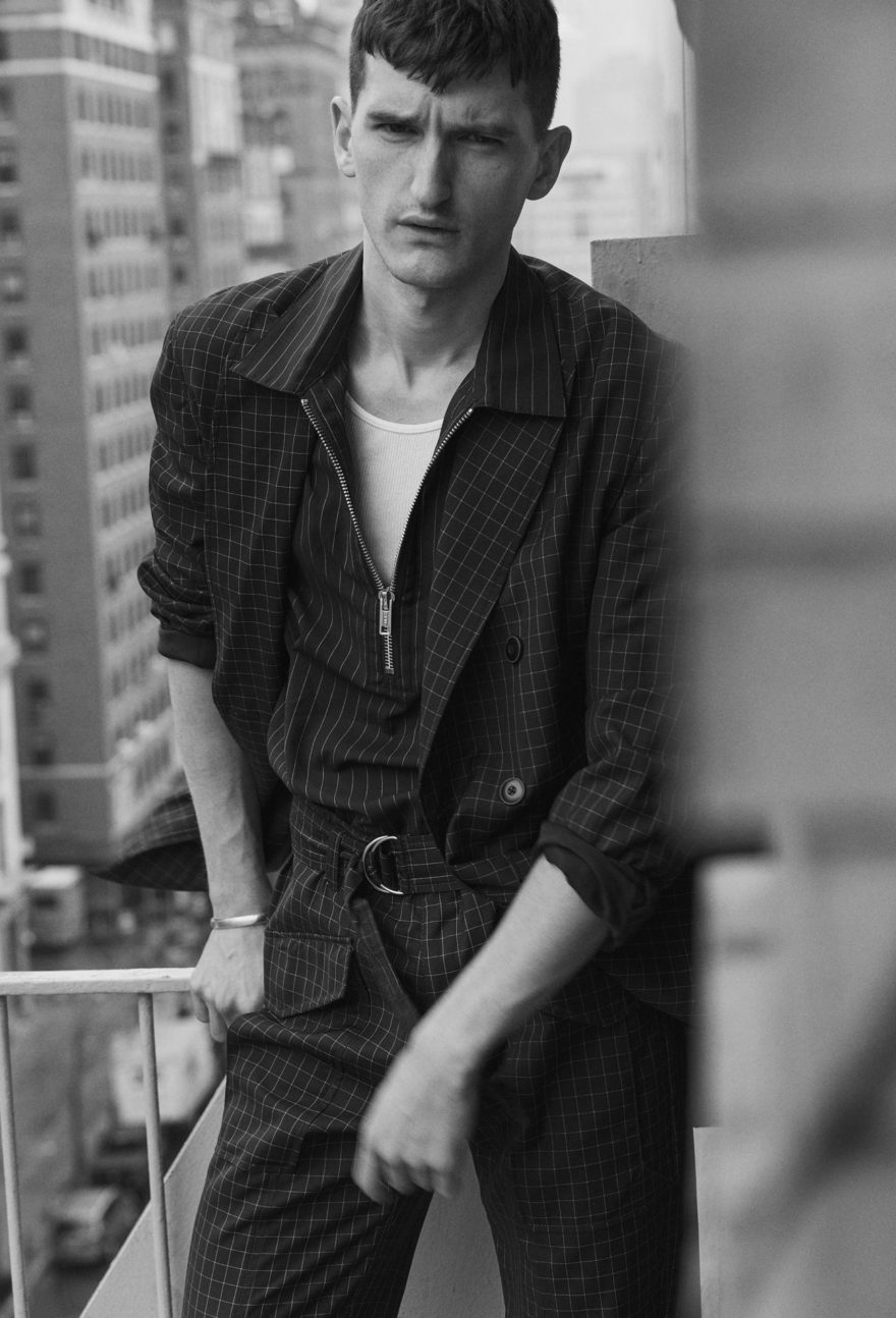 Male Model Andy Nordin stands on fire escape in manhattan gazing into the street in black and white photo.