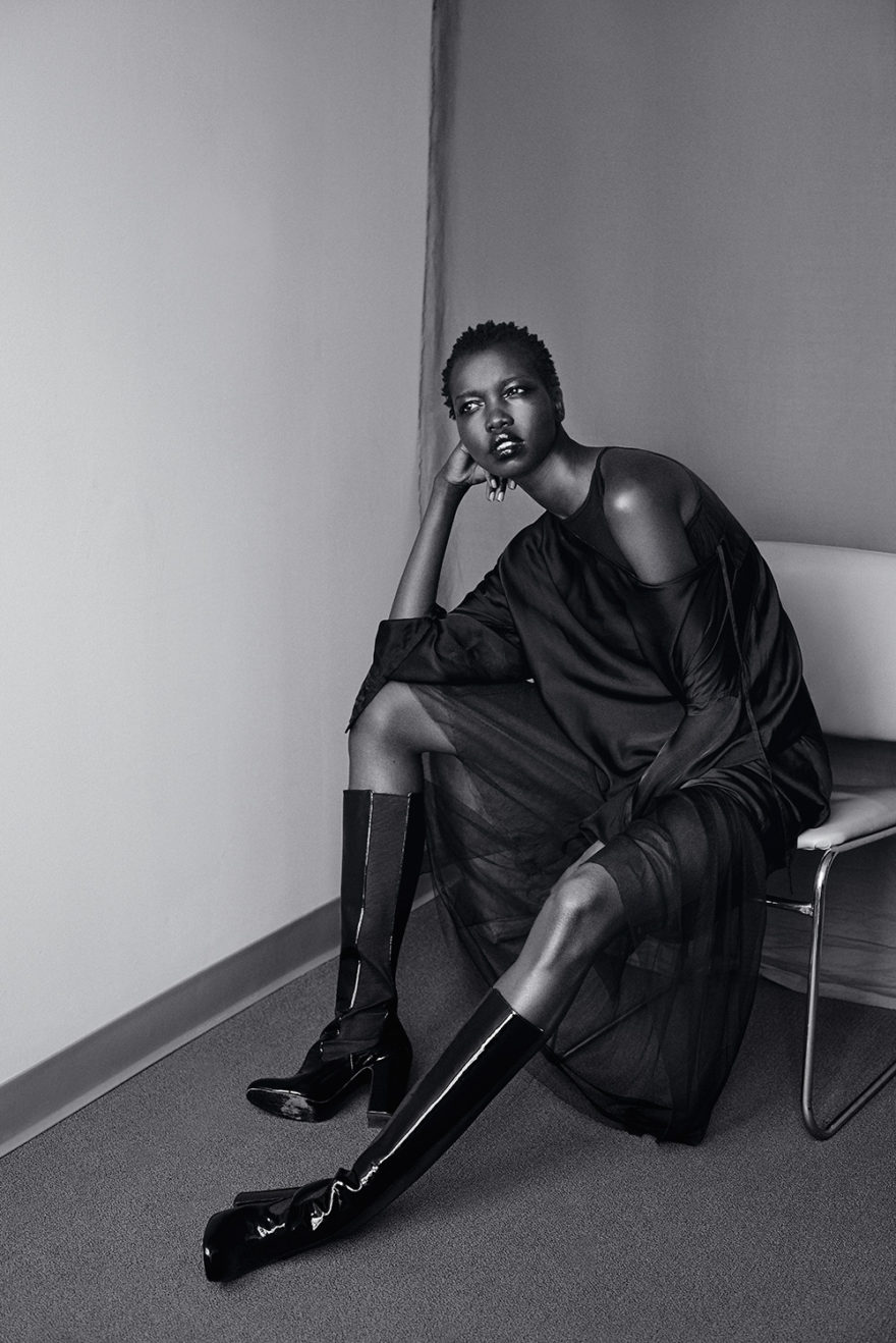 Photo of model Nykhor Paul in office setting sitting on chair. Image of black and white photo.