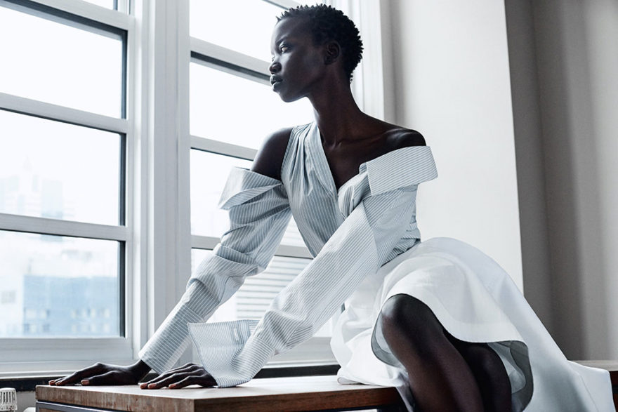 Photo of model nykhor paul sitting on table looking out the window.