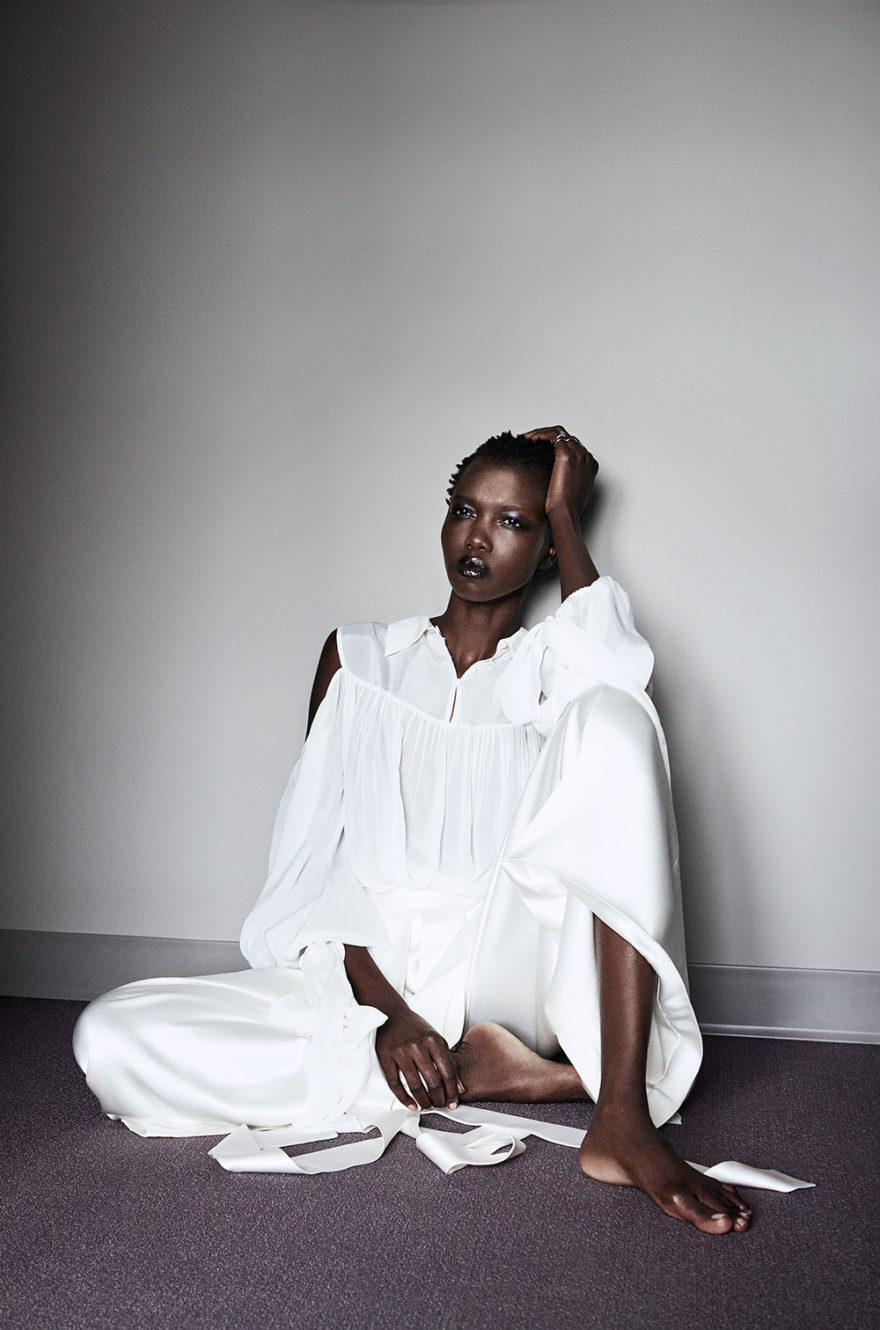 Photo of model nykhor paul sitting on floor looking out the window.