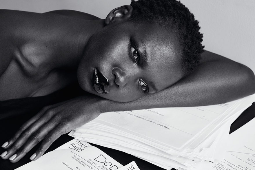 Photo of model Nykhor Paul in office setting. Model is resting her head on the table. Image of black and white photo.
