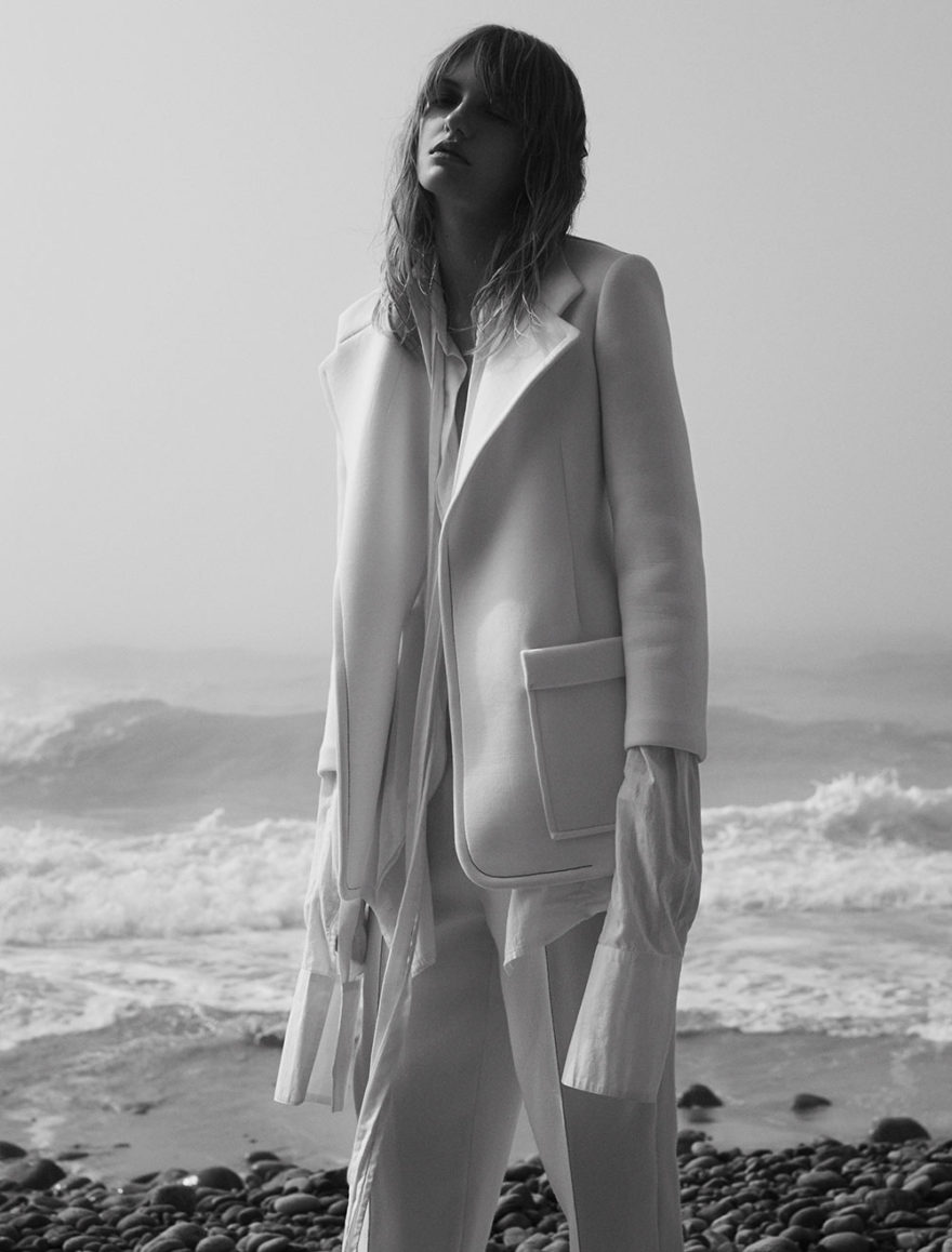 Model Yulia photographed in black and white by photographer Vera Comploj for MONROWE Magazine. White Coat and Trousers by Tamuna Ingorokva White Oversized Shirt by Daniel Gregory Natale