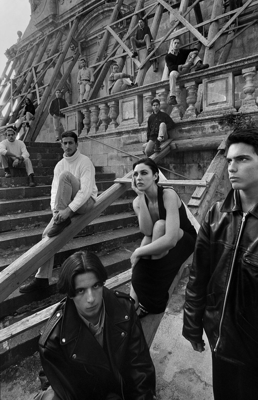 Group of people sitting on steps. Black and white photography. ITALY, Sicily, Palazzolo Acreide with Monica Bellucci. Photo by Ferdinando Scianna. Monica Bellucci