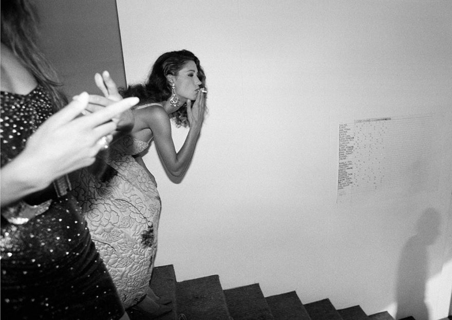 Image of model smoking backstage going down a staircase. Black and white photography. Photo by Ferdinando Scianna