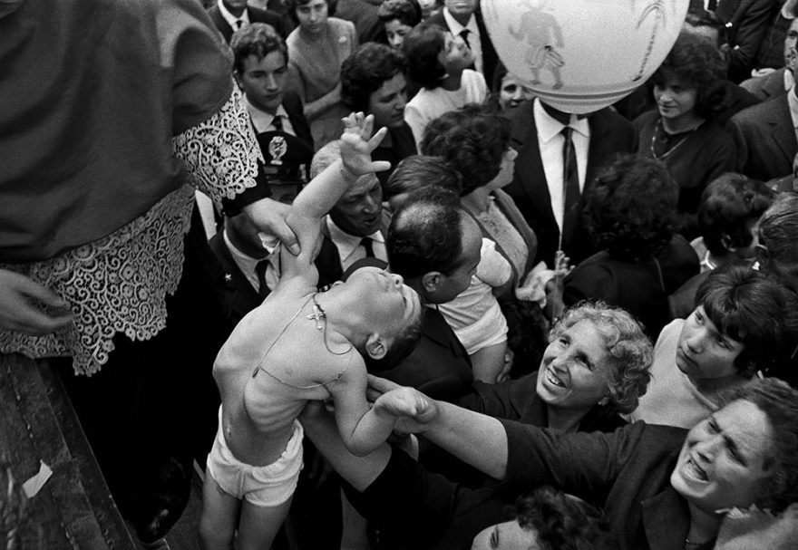 Image of boy being held up in the air, photographed in black and white. Catholic festival of St. Alfio, St. Cirino and St. Filadelfo. 1963. Photo by Ferdinando Scianna