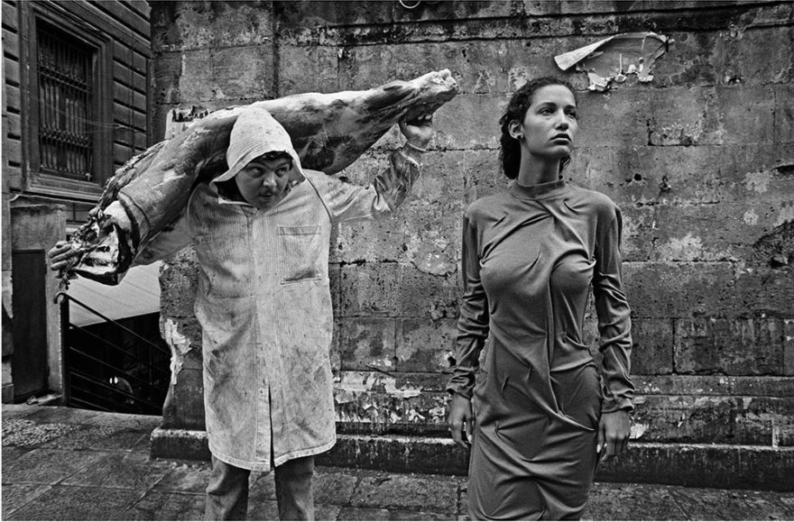 Image of butcher carrying pork over his shoulder. Woman(MARPESSA) standing in the street looking off into distance. Photographed in Black and white in Italy. Dolce Gabana. Photo by Ferdinando Scianna