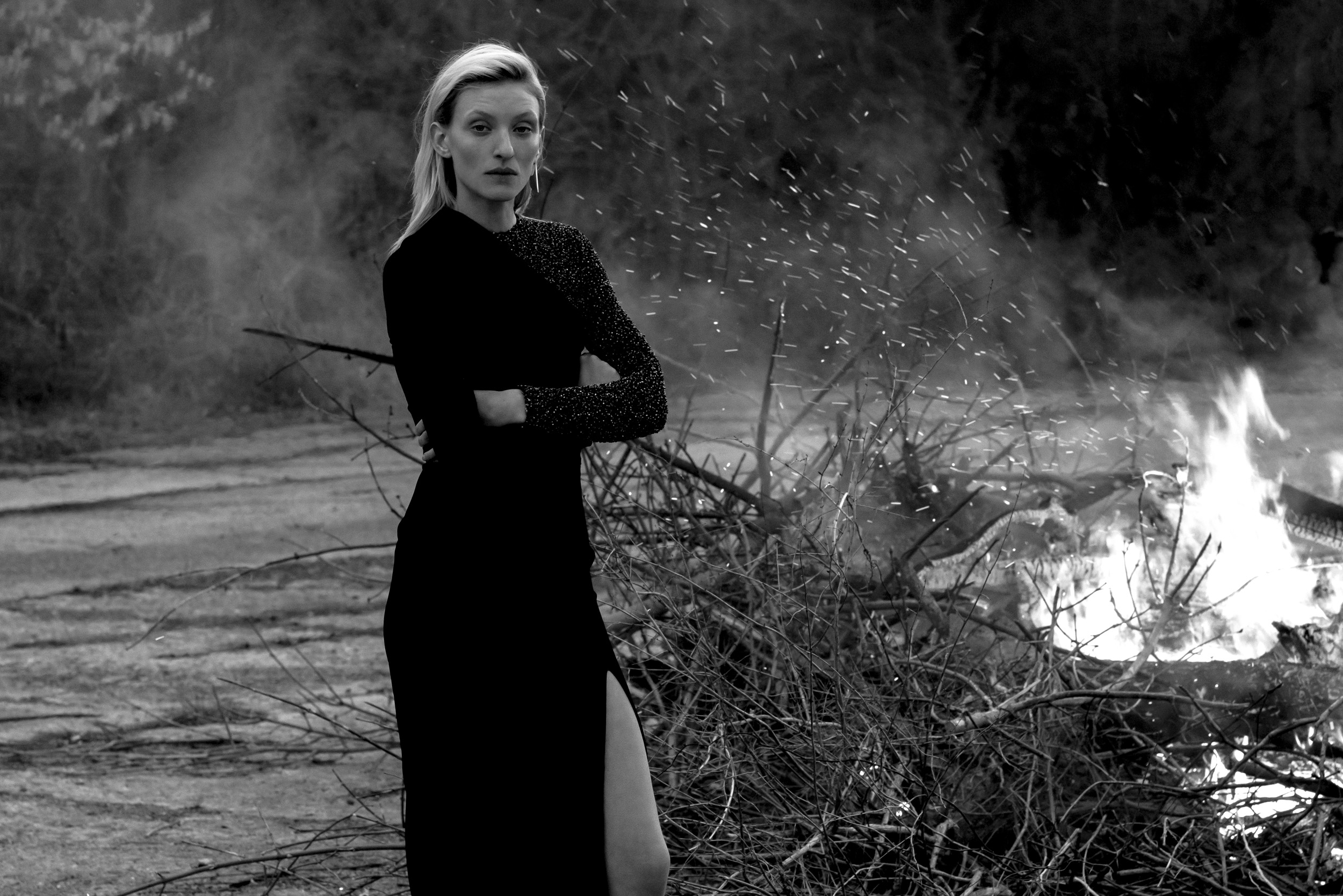 Black and white image of Maggie Maurer shot by Paul McLean. Standing by fire.