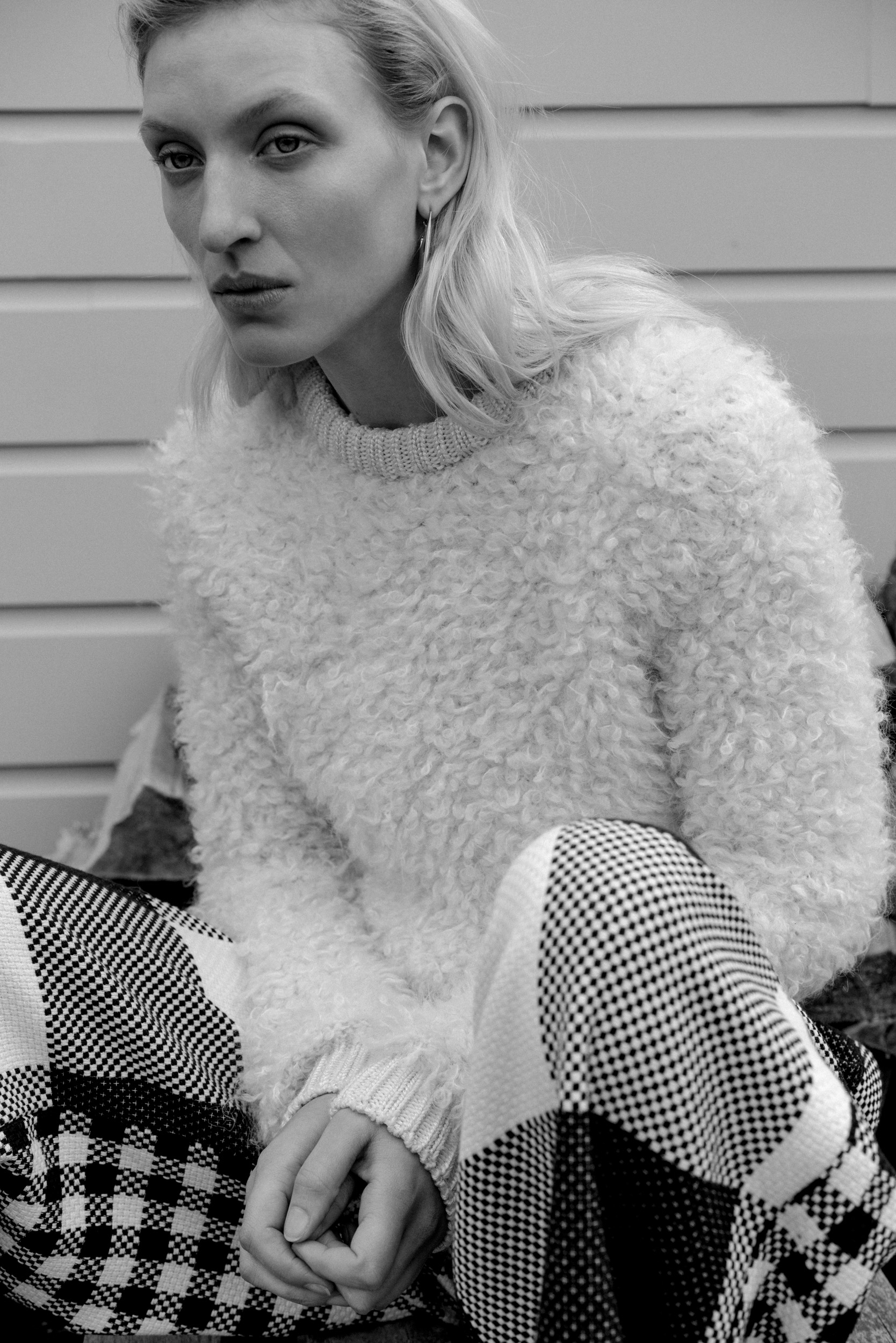 Black and white image of model Maggie Maurer shot by Paul McLean. White mohair knit sweater by CARVEN Black and white check wool trousers by BOSS