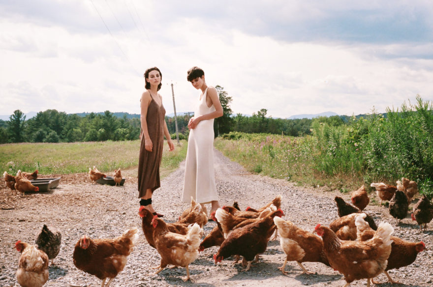 Colored image for MONROWE Magazine by Emily Soto. Models Rose Smith and Maria Kudry on counrt road with hens.