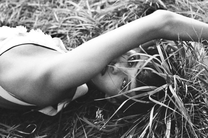 Black and white image by Emily Soto for MONROWE magazine of MUSE model Maria Kudry laying in the grass