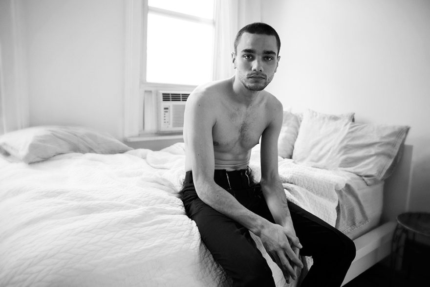 Model Miles Frank sitting on bed without shirt. Photographed by Rami Pyrdol for MONROWE Magazine